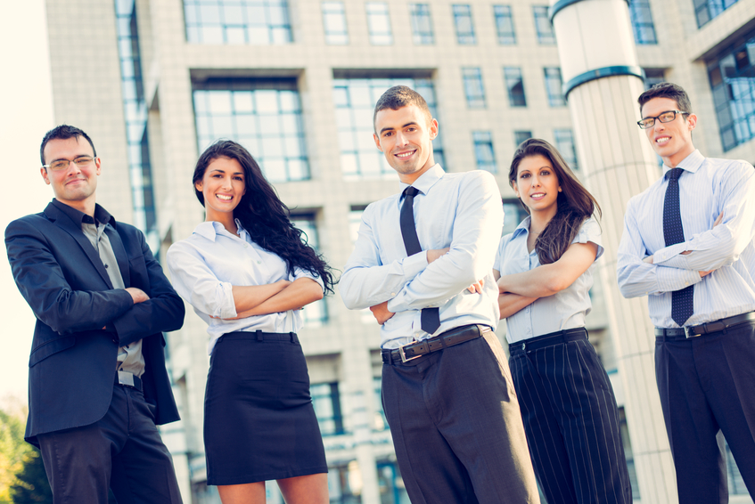 A small group of young business people standing in front of office building with arms crossed and with a smile on their faces looking at camera.